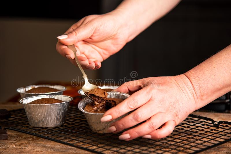Person eating molten chocolate cake. Close up woman closeup lava muffin spoon melted melting hand pudding mold aluminum hot warm female food brown gourmet royalty free stock image