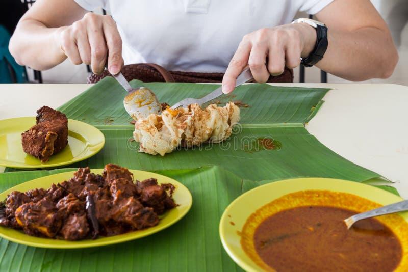 Person eating roti prata, masala mutton, fish on banana leaf royalty free stock image