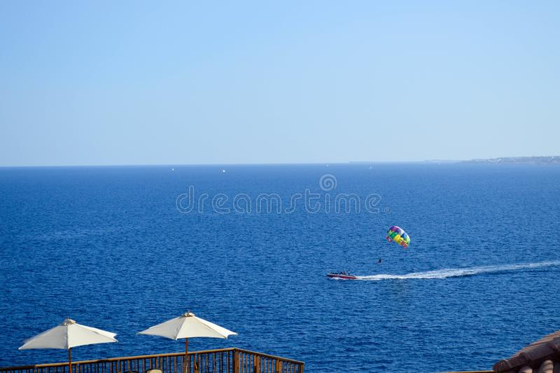 Person is engaged in parasailing, flies on a parachute tied to a boat at high speed on the water at sea in a warm tropical resort. The person is engaged in royalty free stock images