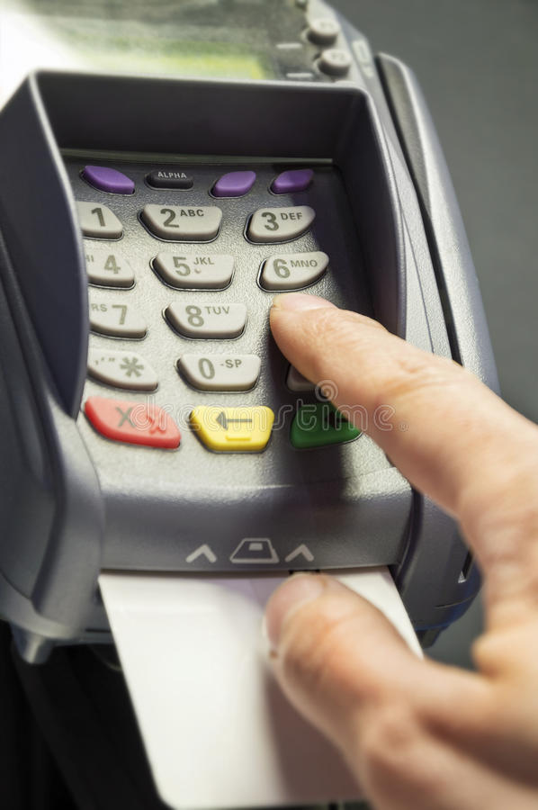Credit card reader and hand. Person entering pin code at credit card reader and white, empty credit card stock image