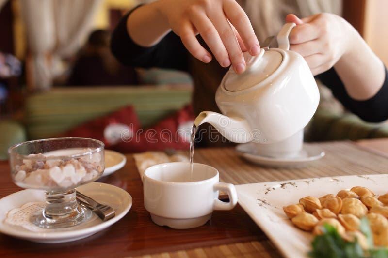 Person füllt Tasse Tee stockfoto