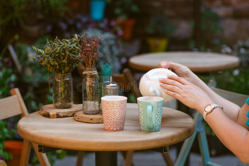 Person füllt Tasse Tee im Café stockfoto