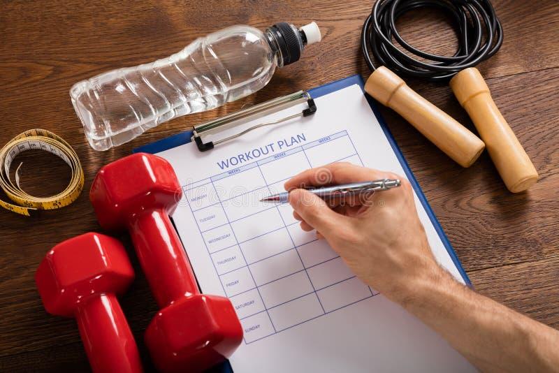 Person Filling Workout Plan Form com equipamentos do exercício imagens de stock royalty free
