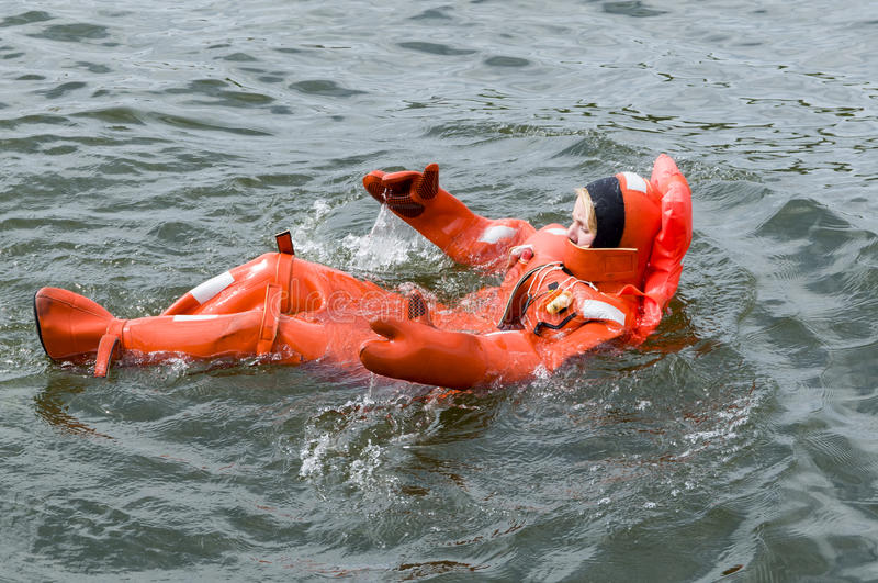 Person floating in survival suit. Person floating in immersion survival suit a waterproof dry suit that protects the wearer from hypothermia from immersion in stock images