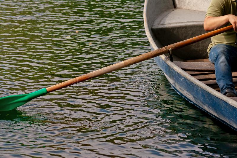 The person floats on the rowboat on a surface of the water. In summer day royalty free stock photo