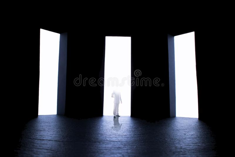 Person with a flooded with light face standing inviting by hand to make a choice, concept religion. Person with a flooded with light face standing in one of royalty free stock photo