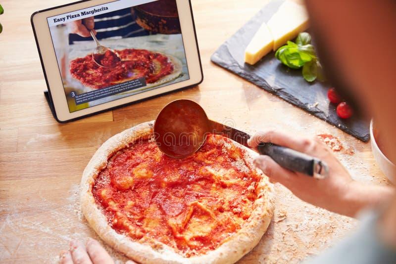 Person Following Pizza Recipe Using App en la tableta de Digitaces fotos de archivo