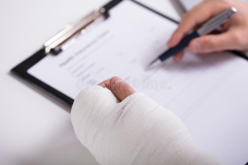 Person With Fractured Hand Filling Health Insurance Form. High Angle View Of A Person With Fractured Hand Filling Health Insurance Form royalty free stock images