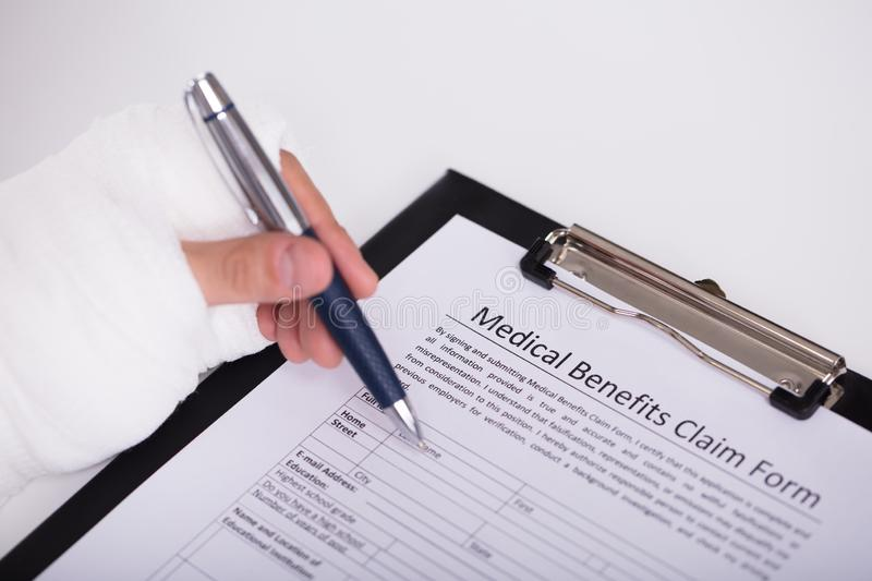 Person With Fractured Hand Filling Medical Benefit Claim Form. Close-up Of A Person With Fractured Hand Filling Medical Benefit Claim Form royalty free stock photography