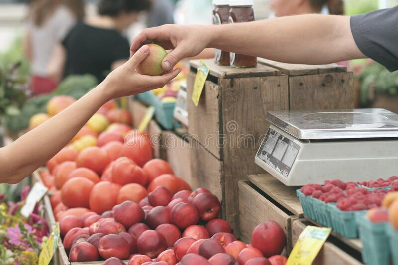 Person Giving Fruit to Another stock photography
