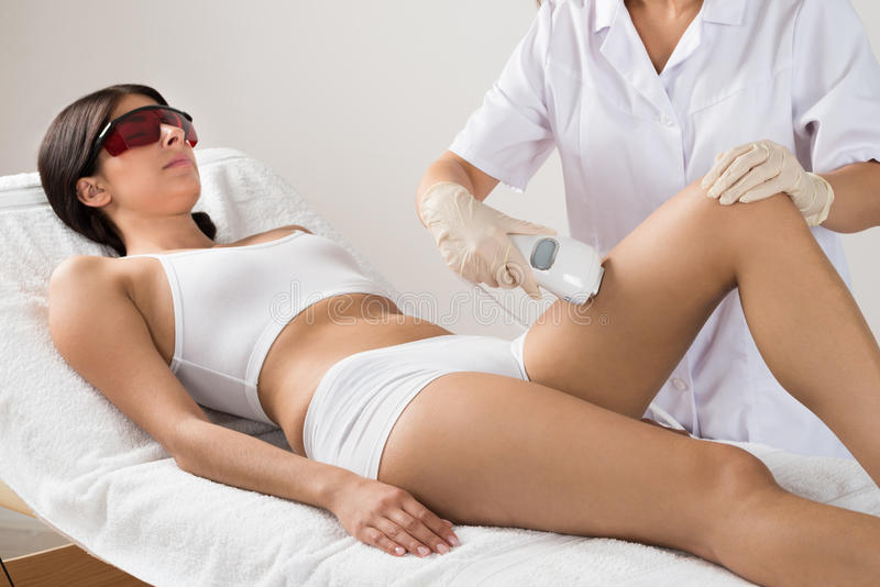 Person giving laser therapy to woman stock photo
