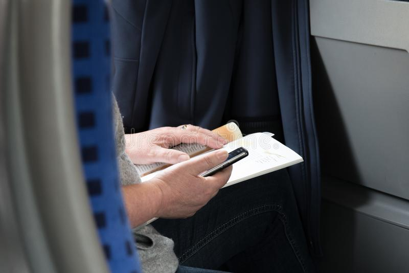 Person in Gray Shirt Holding Black Smartphone and Brown Book stock photography