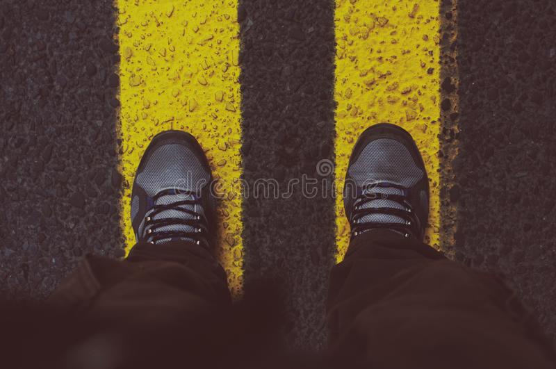 Person in Gray Sneakers Standing on Pedestrian Lane stock images