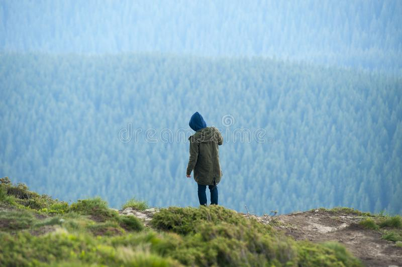 Person in Green Jacket Standing on Cliff royalty free stock photography