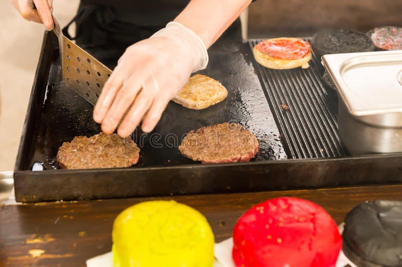 Person grilling beef patties on a griddle. Person wearing gloves grilling beef patties for hamburgers on a commercial griddle using a spatula with brightly stock photo