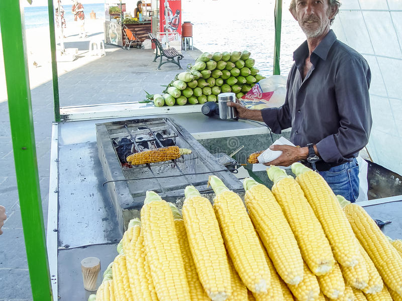 Person grilling corn on the cob in Rhodes. Rhodes, Greece - august 31, 2011: Person grilling corn on the cob in Rhodes island, Greece royalty free stock photo