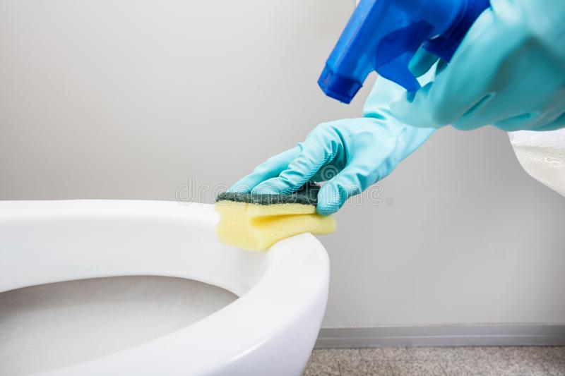 Person Hand Cleaning Toilet Using-Spons stock fotografie