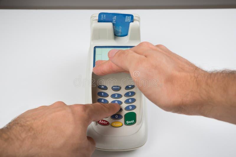 Person Hand Entering Code In um leitor de cartão fotografia de stock royalty free