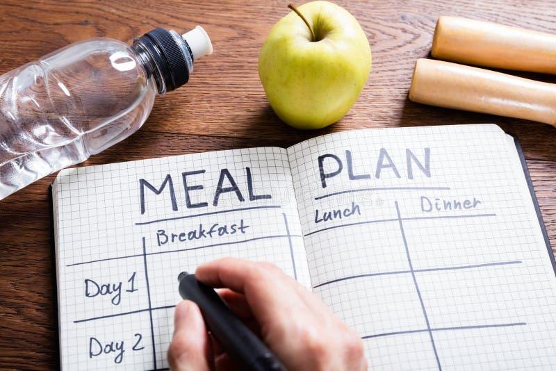 Person Hand Filling Meal Plan im Notizbuch stockbild