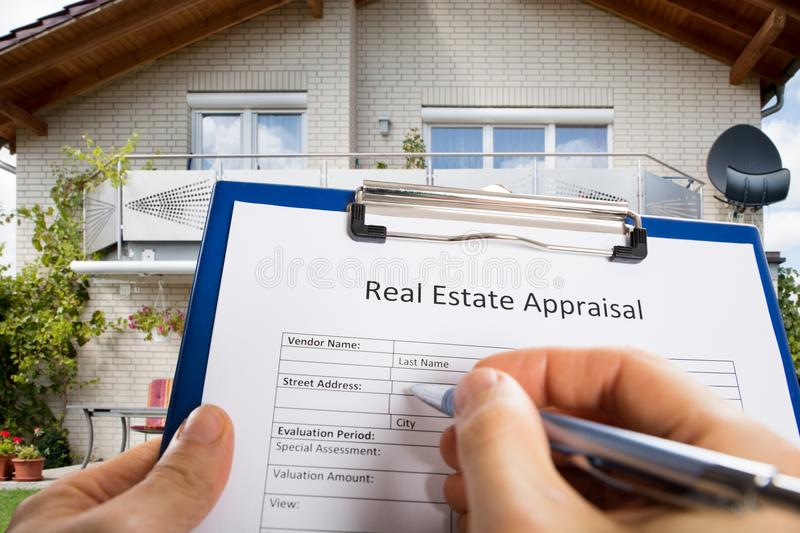 Person Hand Filling Real Estate Appraisal Document stock photo
