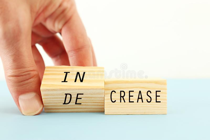 person hand flipping wooden cubes so that it will be written increase instead of decrease. business development and positive. stock images
