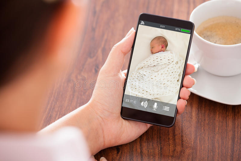 Person Hand Holding Babyphone imagens de stock royalty free