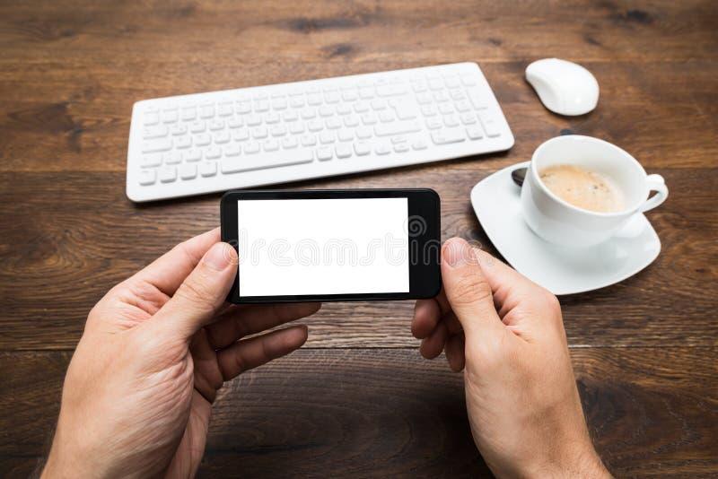 Person Hand Holding Mobile Phone på skrivbordet royaltyfria bilder