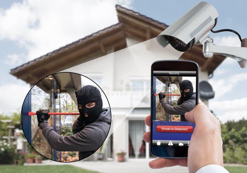 Person Hand Holding Mobile Phone que detecta o assaltante imagens de stock royalty free