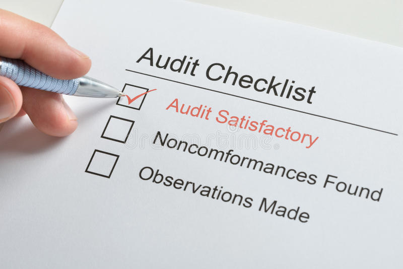 Person hand making tick in audit checklist stock photo