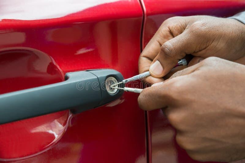 Person Hand Opening Car Door med Lockpicker royaltyfria bilder