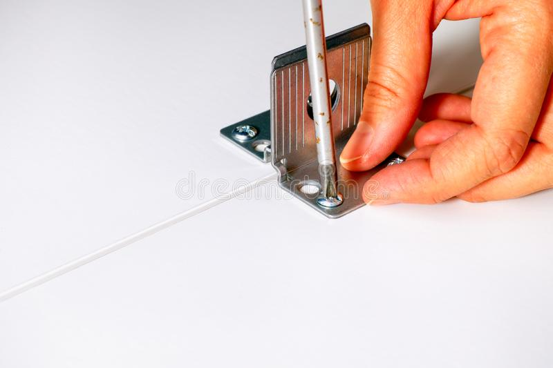 Person hand with screwdriver twisting the into the furniture. Close-up stock photo