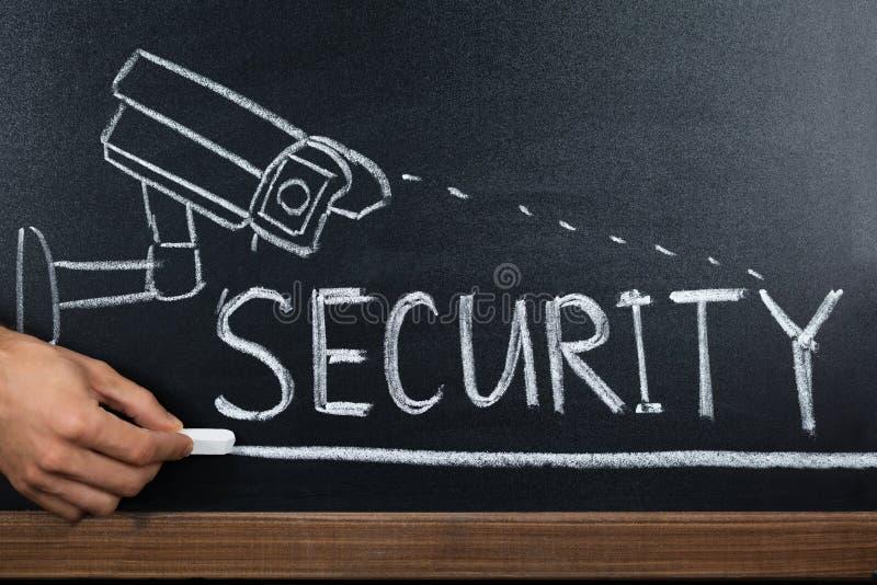 Person Hand Showing Security Concept sur le tableau noir images stock