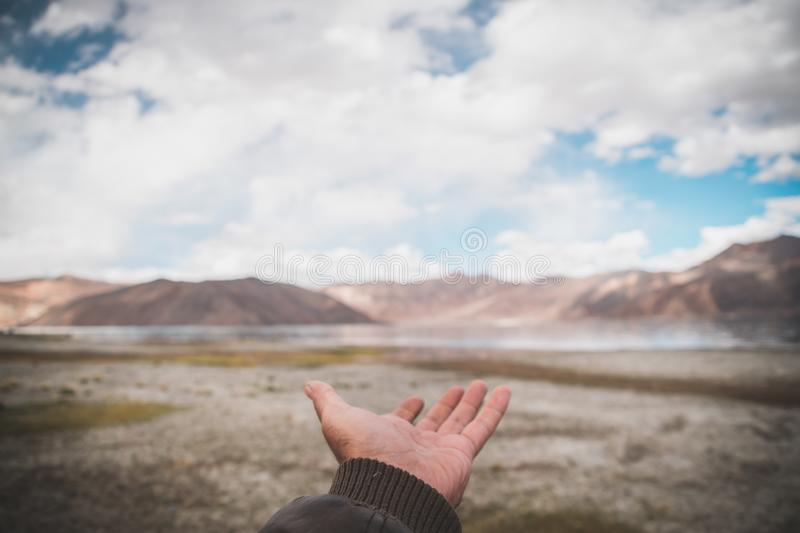 person hand showing view of mountains lake cloudy skies royalty free stock images