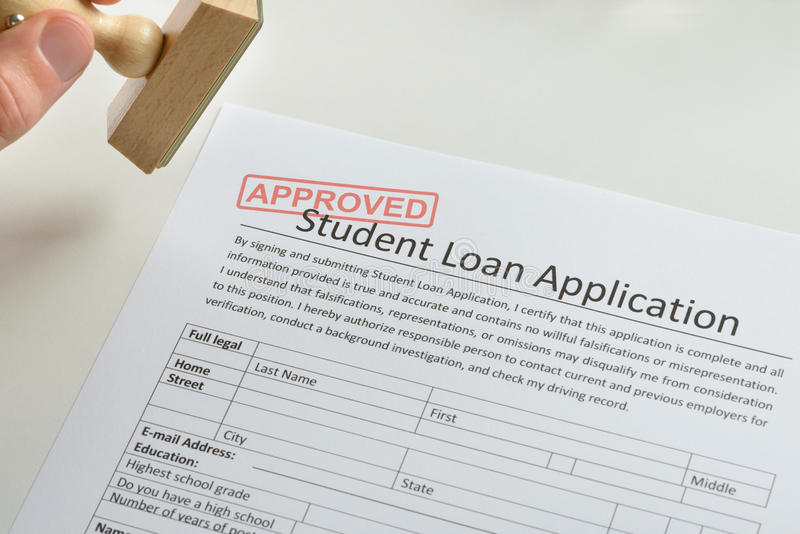 Person Hand With Stamp And Approved Loan Application. Close-up Of Person Hand With Rubber Stamp And Approved Student Loan Application royalty free stock photos