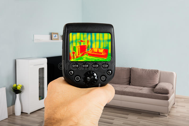 Person Hand Using Infrared Thermal Camera In Living Room. Close-up Of Person Hand Using Infrared Thermal Camera In Living Room At Home royalty free stock photography