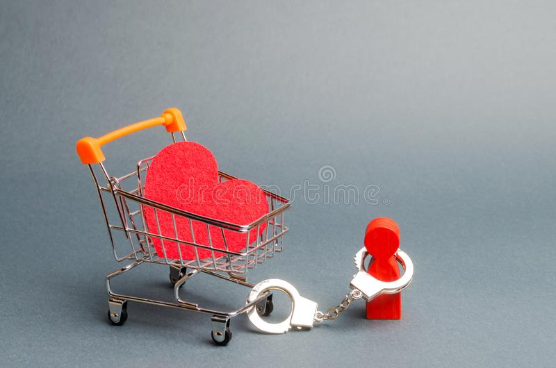 Person is handcuffed to a red heart on a supermarket cart. Man is limited in freedom of action. Difficulties in love. Non-reciprocal love. Organization of stock image