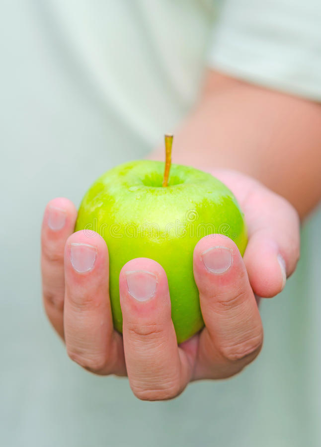 A person is handing green apple for you. Here is an apple for you. A person is handing green apple for you stock photo