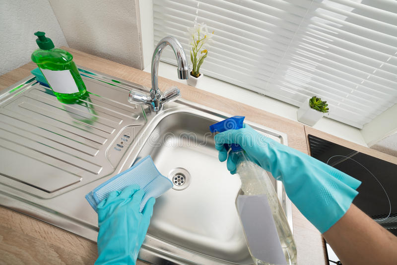 Person hands cleaning kitchen sink. Person Hands In Blue Glove Cleaning Silver Kitchen Sink stock photos