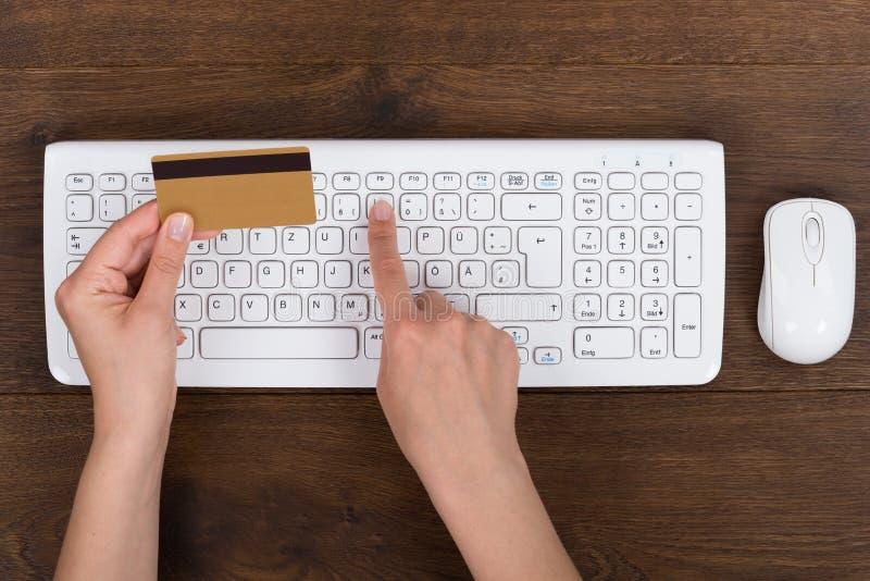 Person Hands With Credit Card en Computertoetsenbord royalty-vrije stock afbeelding