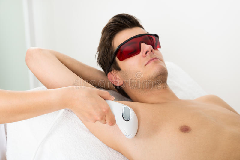 Person Hands Giving Laser Epilation Therapy To Man stock photo