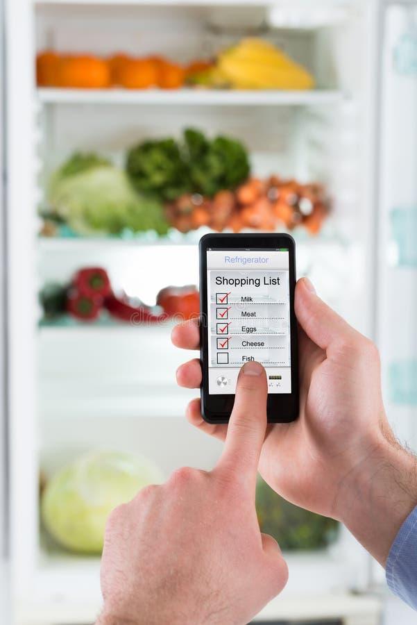 Person Hands Making Shopping List au téléphone portable images libres de droits