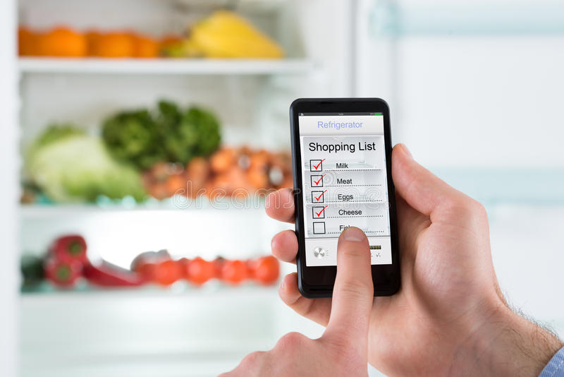 Person Hands Marking Shopping List auf Handy-Anzeige lizenzfreies stockbild