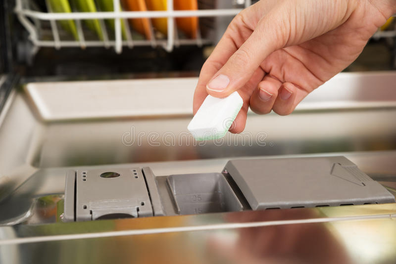 Person Hands Putting Dishwasher Tablet in Afwasmachine Box royalty-vrije stock afbeeldingen