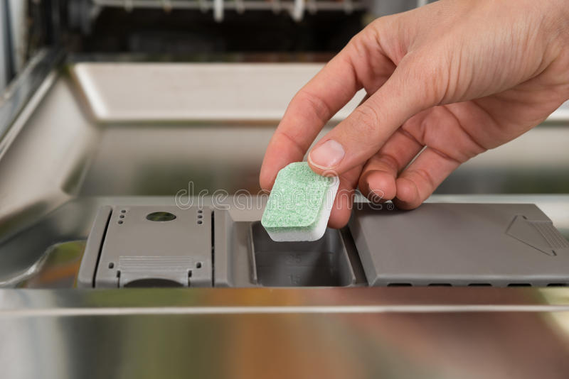 Person Hands Putting Dishwasher Tablet in Afwasmachine Box stock afbeelding
