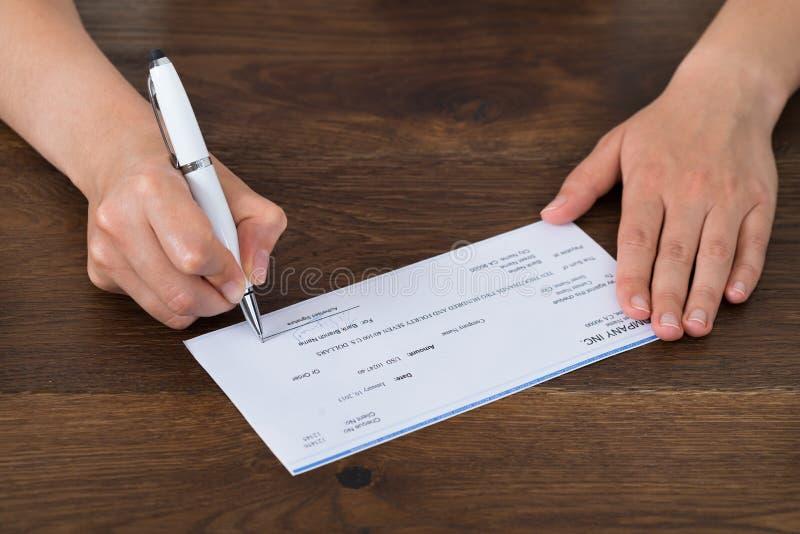 Person Hands Signing Cheque royaltyfria bilder