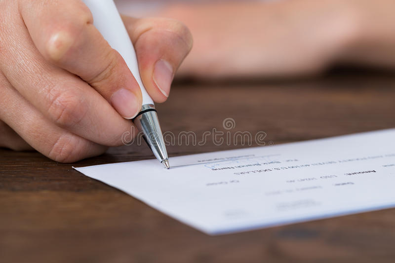 Person Hands Signing Cheque royaltyfri foto