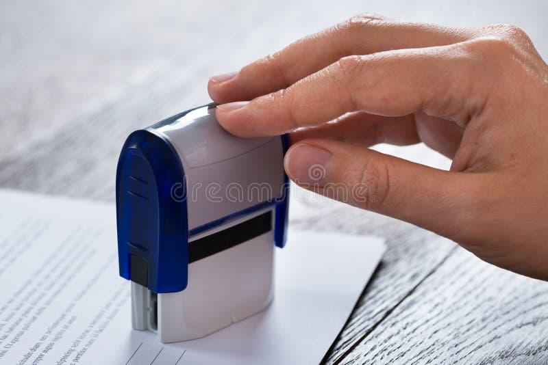 Person Hands With Stamper And-Dokument lizenzfreies stockbild
