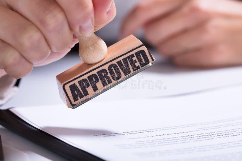 Person Hands Using Stamper On-Dokument mit dem Text genehmigt lizenzfreie stockfotografie