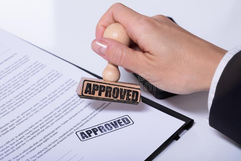 Person Hands Using Stamper On-Dokument mit dem Text genehmigt stockfoto