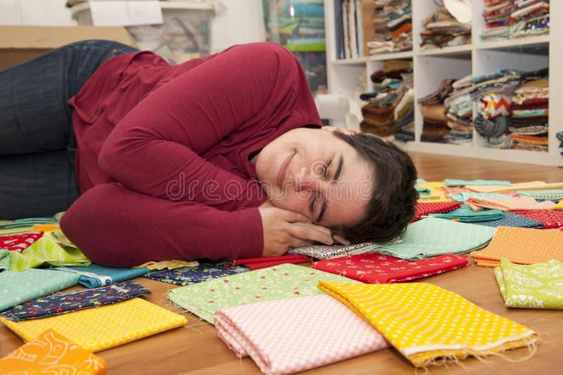 Asleep and exhausted in fabric. Person has fallen asleep in their pile of fabric in the craft room royalty free stock photos